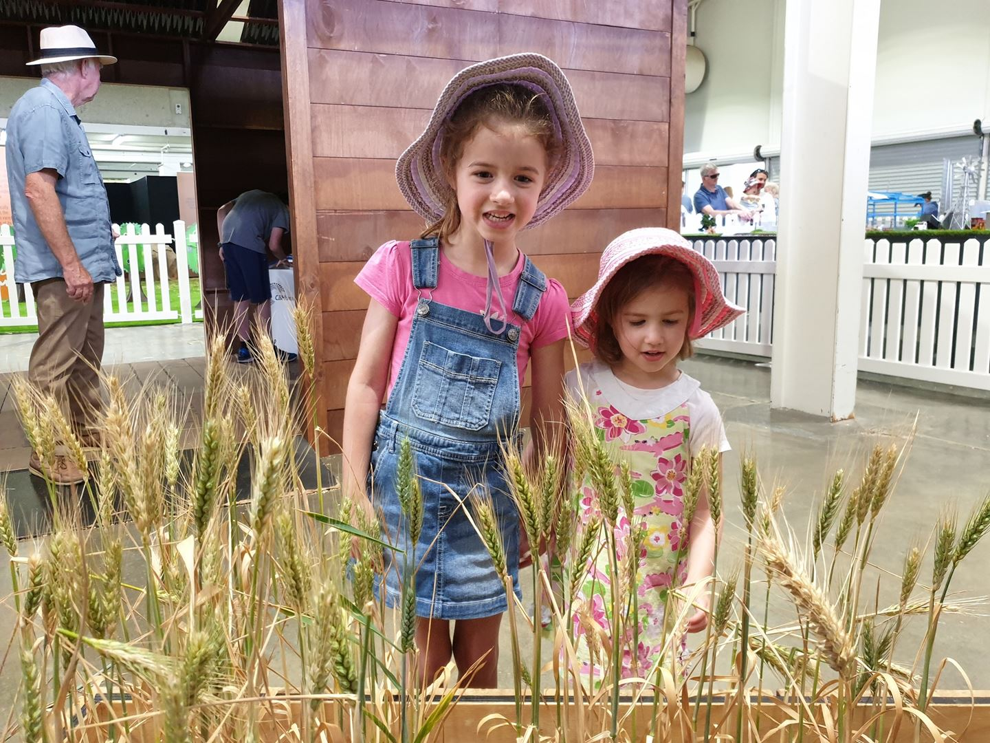 Two young girls wearing floral hats stand behind a planter box of wheat smiling at the camera