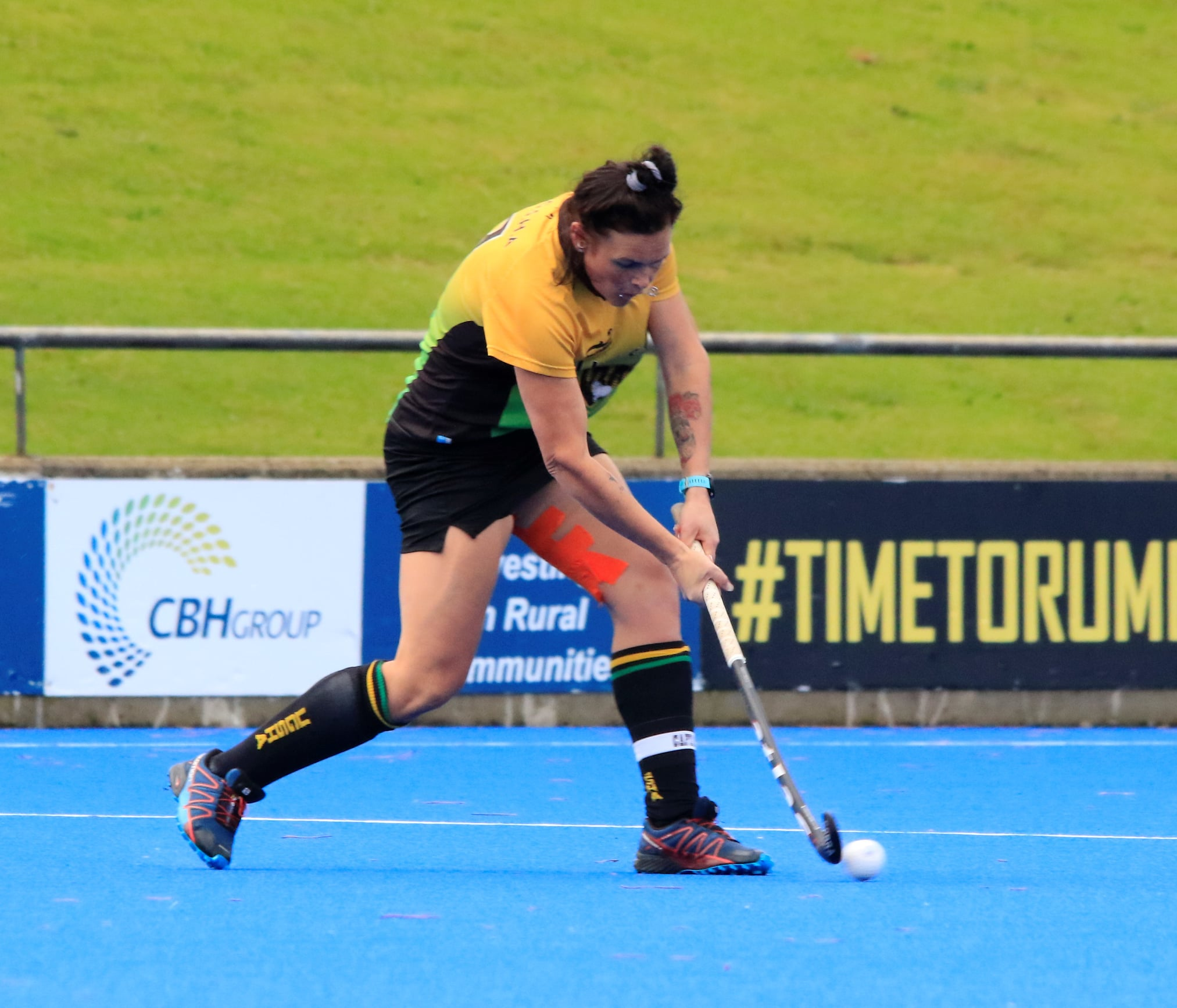 A girl wearing a yellow and green uniform swings a hockey stick