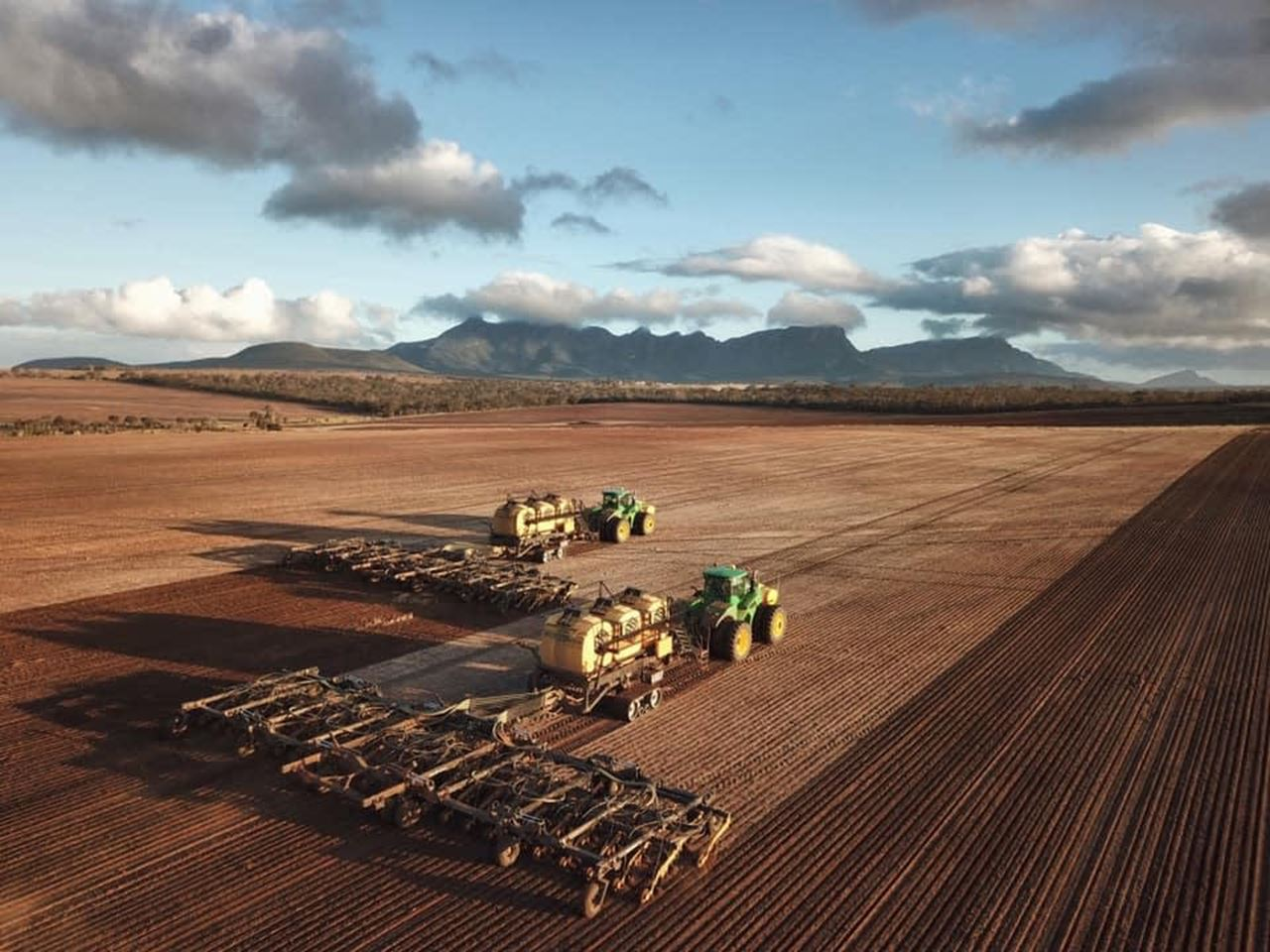 Two green tractors pulling two seeders work side by side in a reddish brown paddock