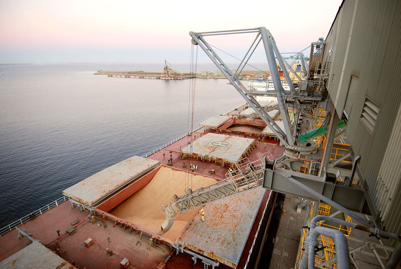 A ship is being loaded with grain at the Esperance Grain Terminal with a sunset in the background