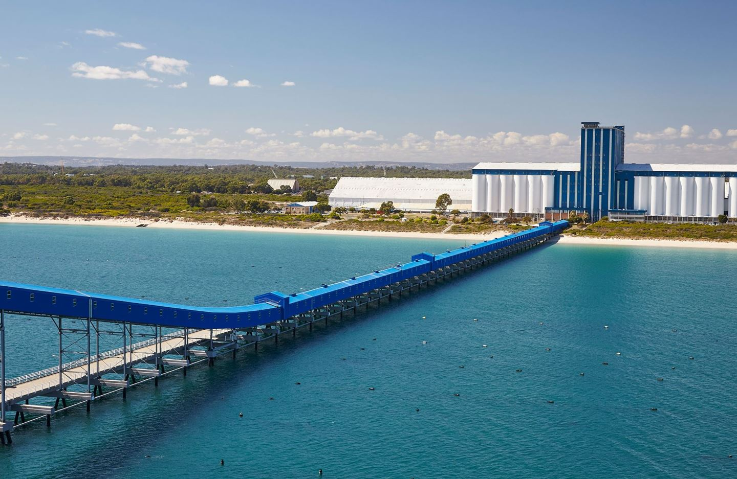 A large blue and white terminal has a long blue jetty stretching out to sea