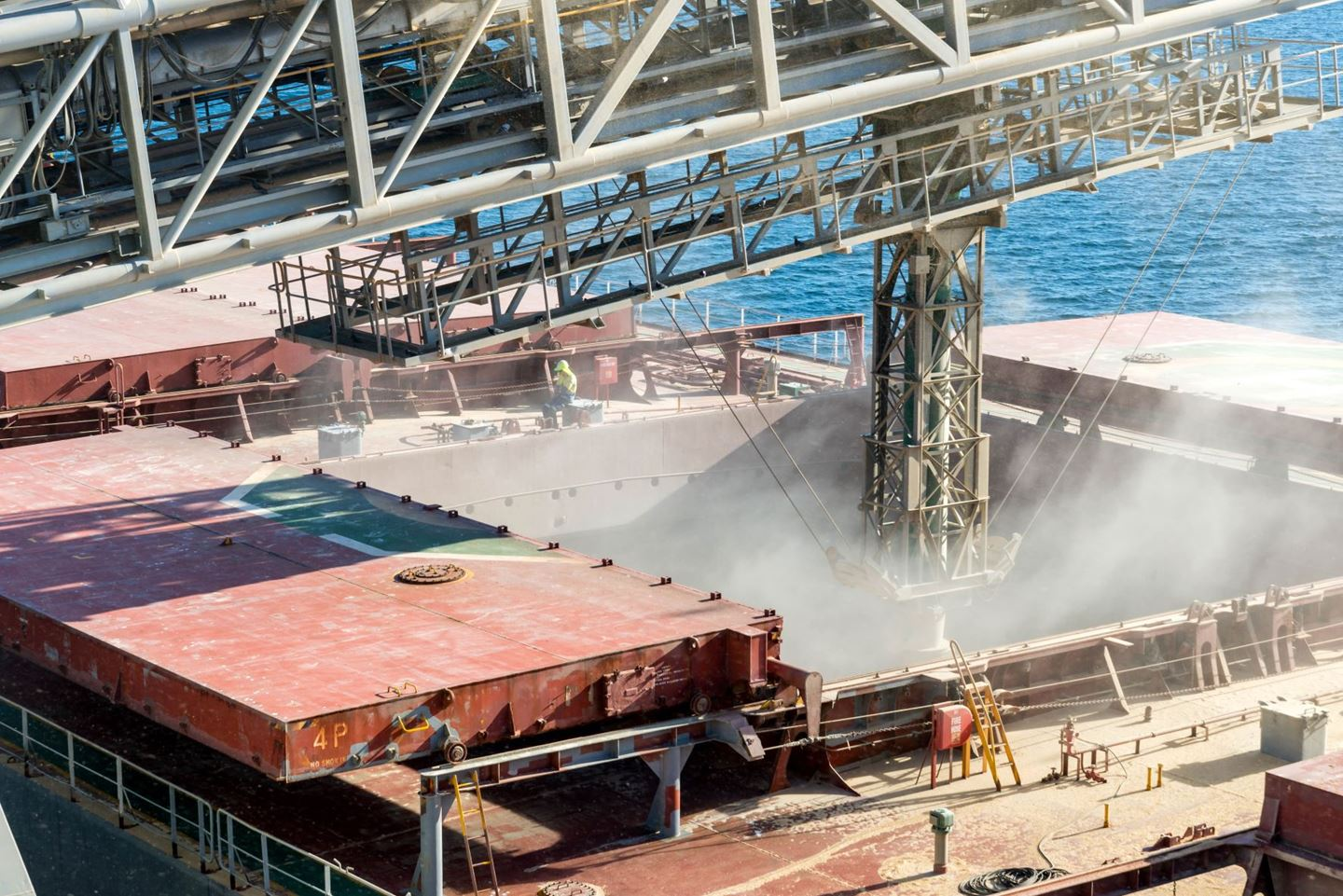 A shiploading structure discharges grain into the open hatch of a ship, grain dust is flying everywhere