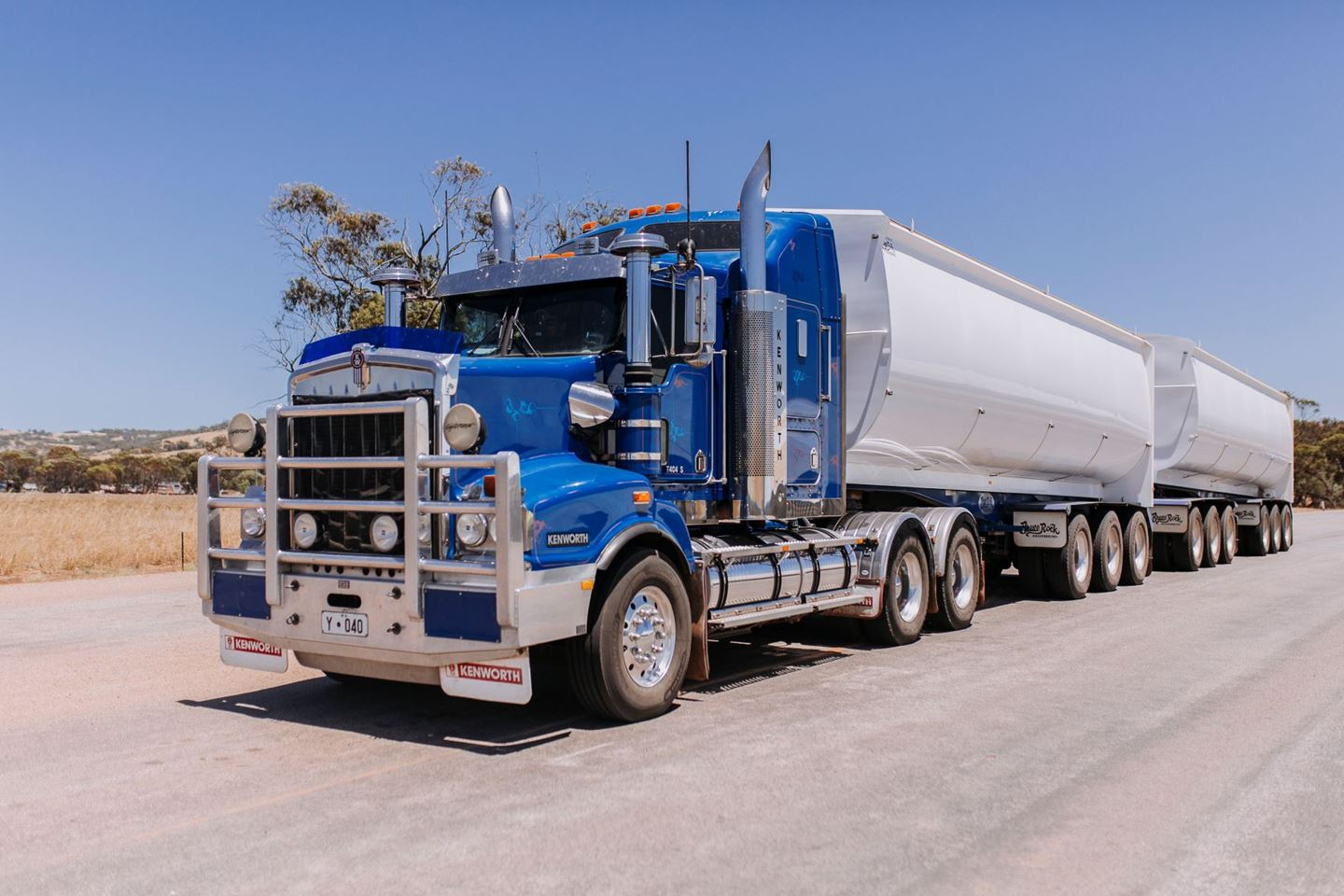 A large blue truck parked on a gravel road