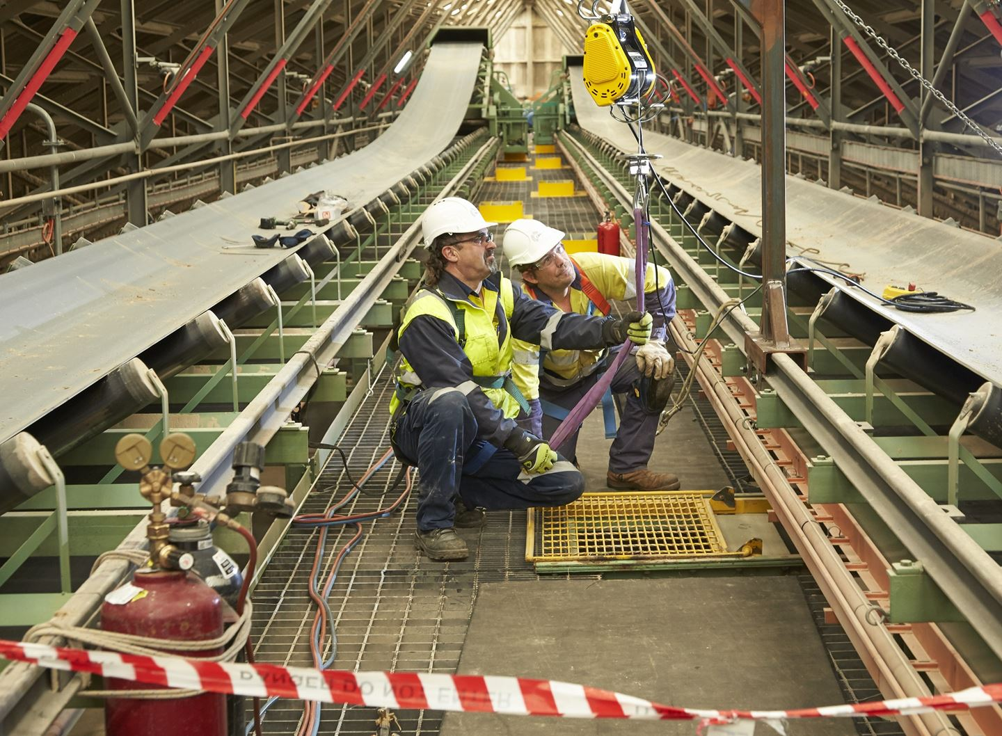 Two men in work clothing inspect a strap between two conveyor builts
