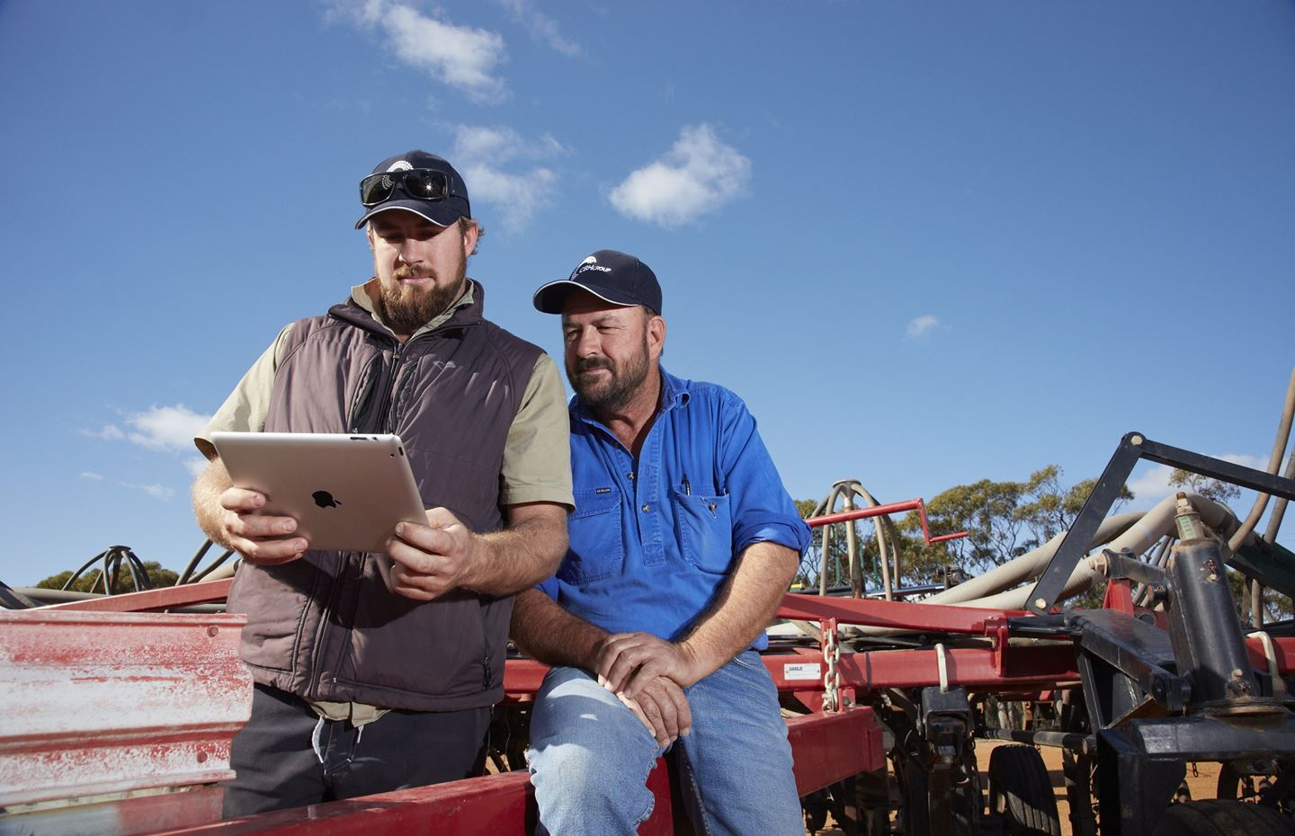 Two men wearing caps sit on a red tractor while looking at an ipad together