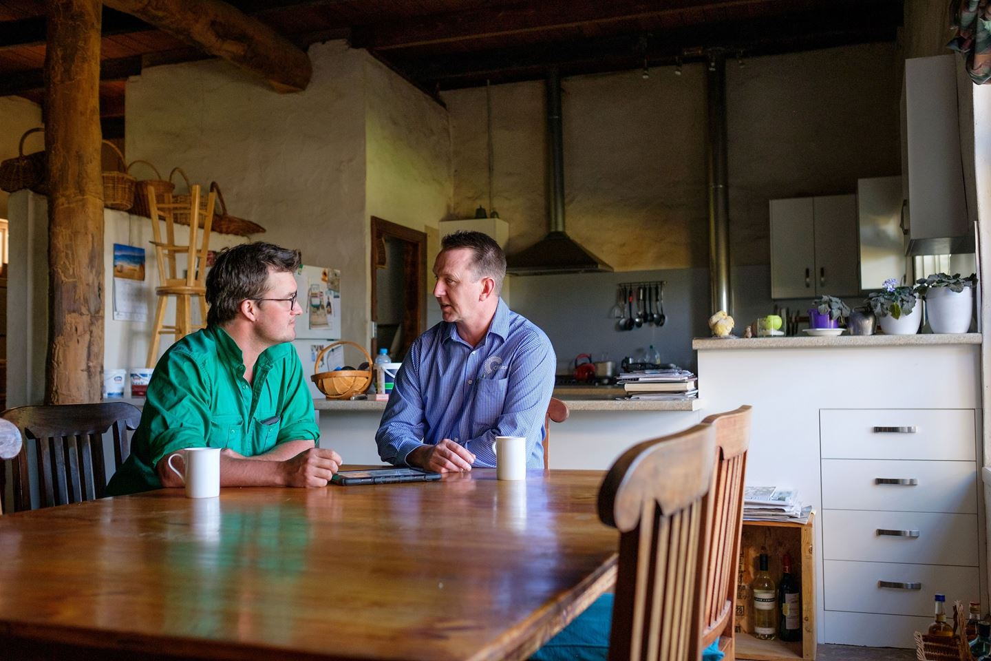 A man in a green shirt and a man in a blue shirt sit at a kitchen table chatting with coffee mugs in front of them